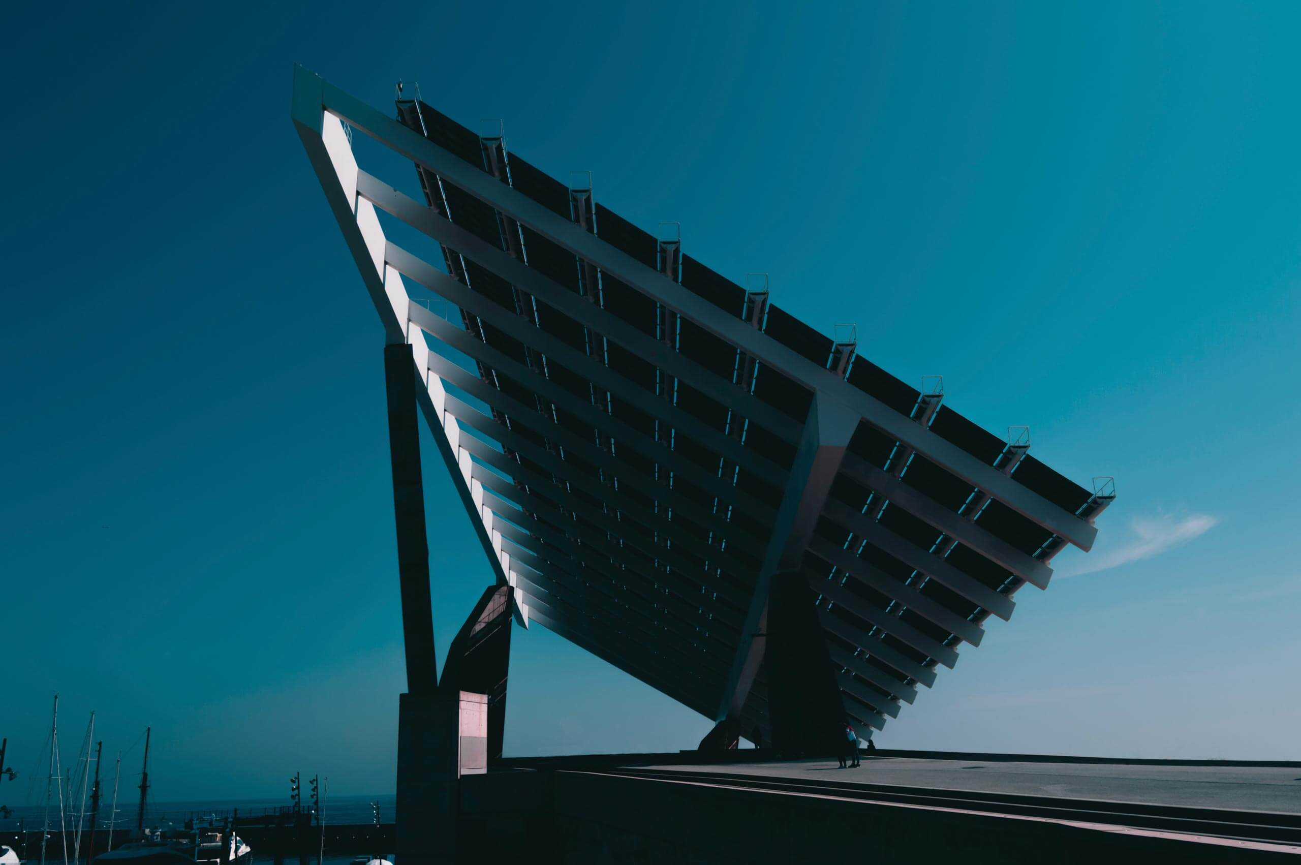 A large-scale solar panel installation faces towards the sun on a beautiful, clear day