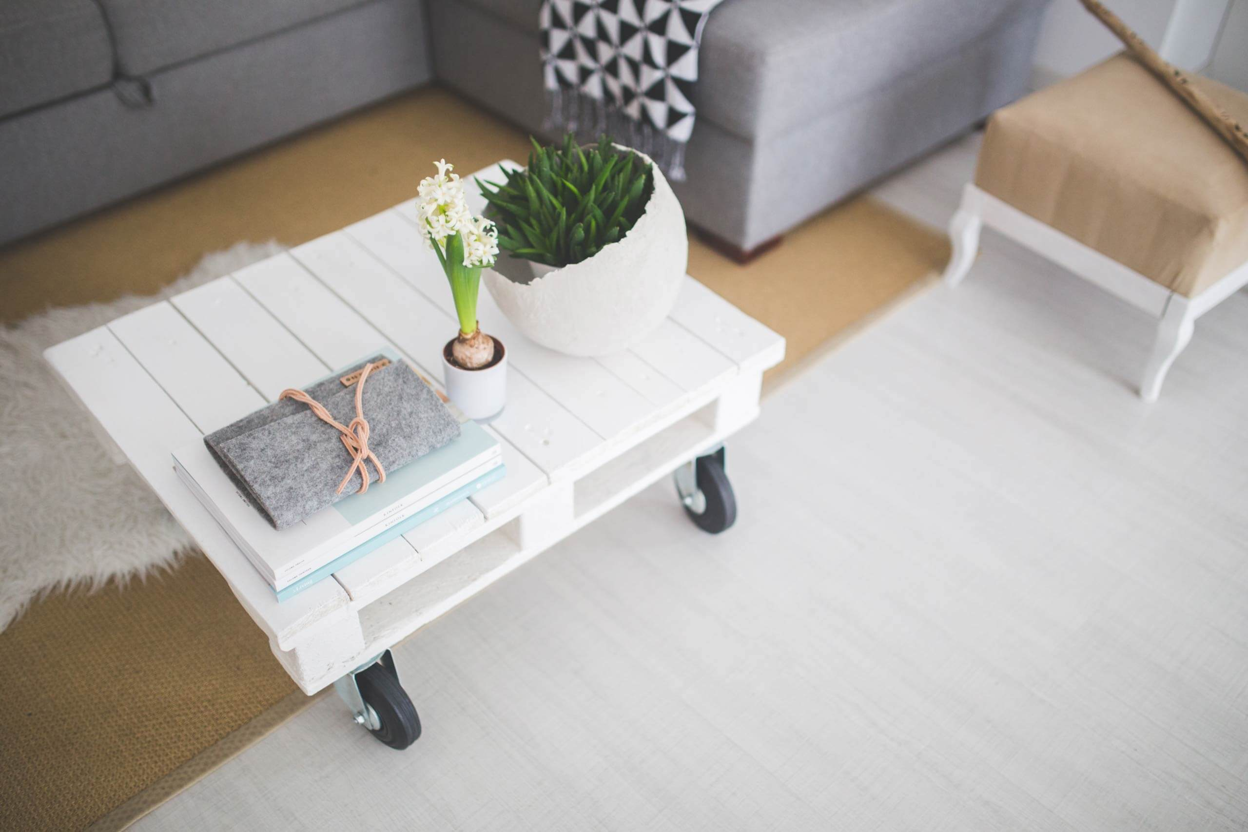 A homemade coffee table sits in the middle of a living room coated in soft, pastel colours.
