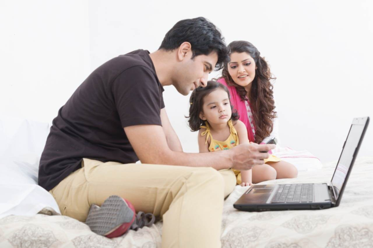 A young couple with their daughter sit on their bed, looking at a laptop.