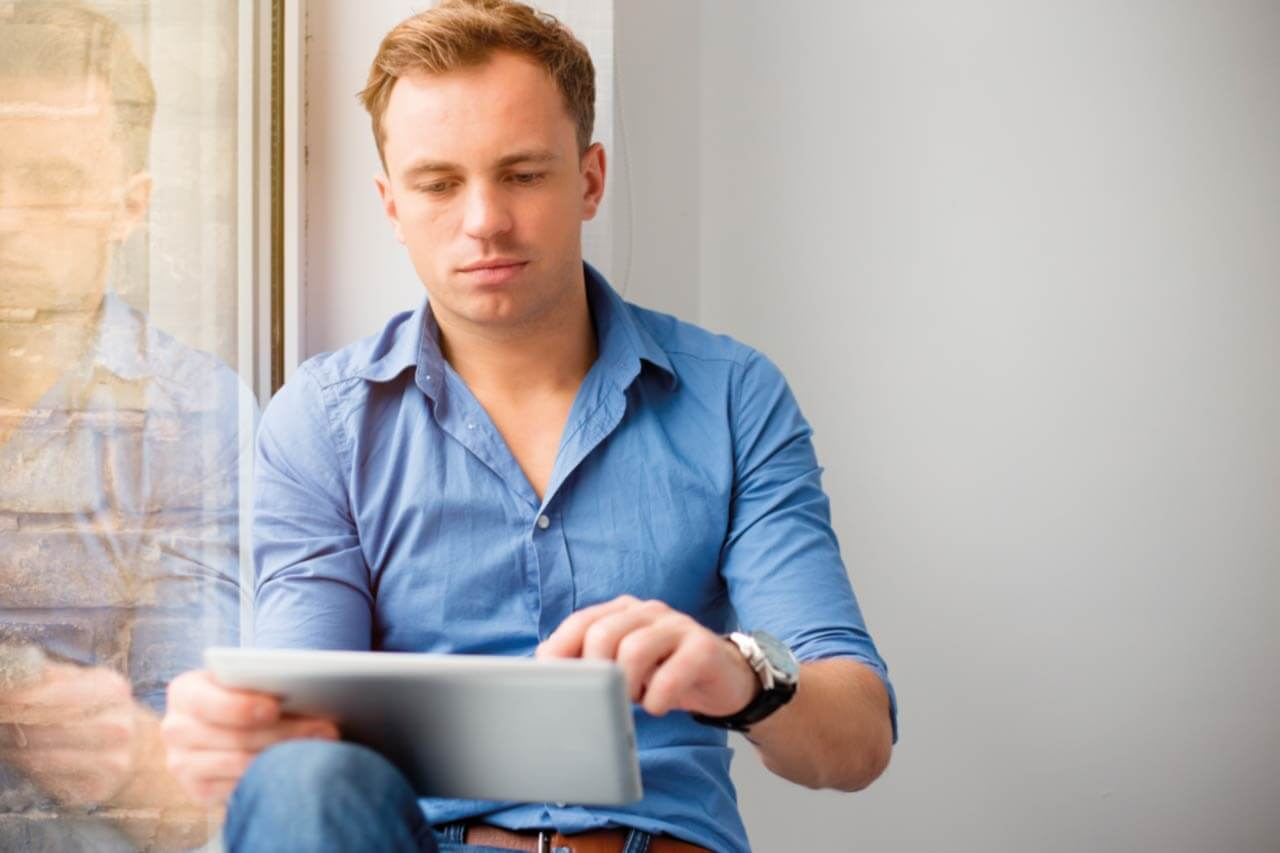 A young man sits by a windowsill, relaxed, using his iPad.