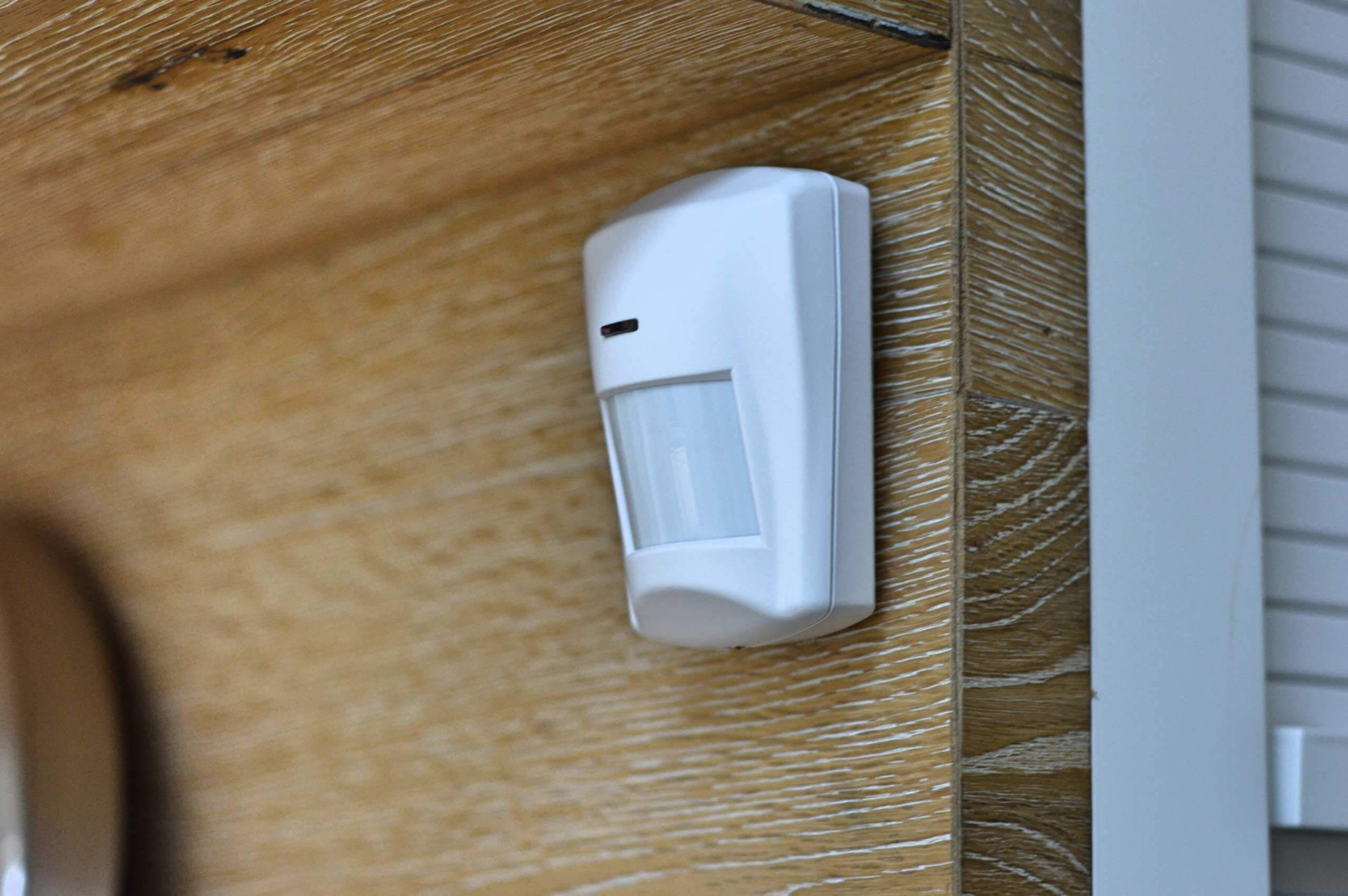 The motion sensor component of a home automation package clipped onto a modern wooden wall