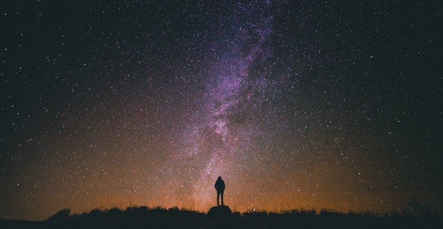 A lone figure stands staring up at the starry night sky